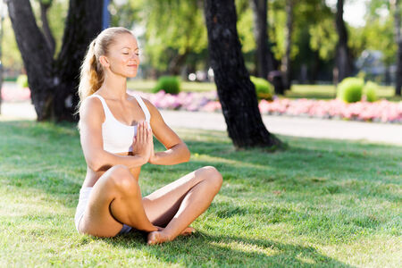 Young woman in white sitting on grass in lotus pose photo