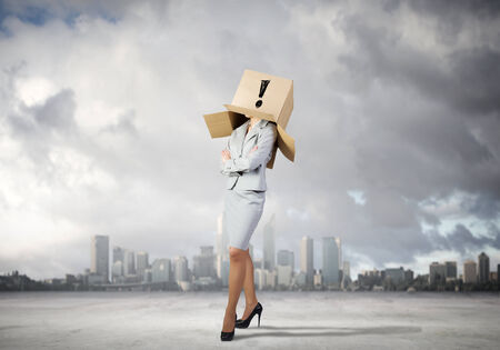 hidden success: Businesswoman wearing on head carton box with sign Stock Photo