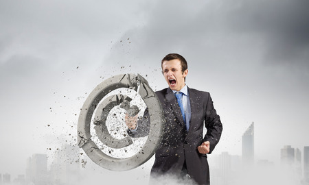 Angry businessman crashing stone trademark with karate kick photo