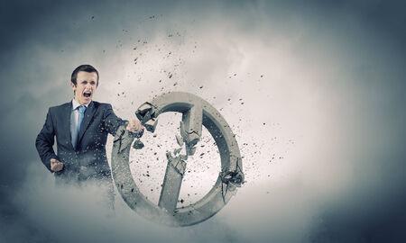 Angry determined businessman crashing stone prohibition symbol Stock Photo