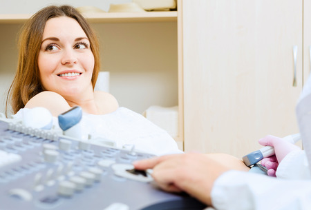 Young pregnant woman examined by doctor at ultrasound check