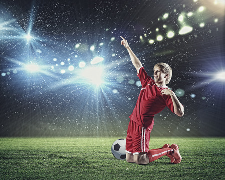 Football player standing on knees and screaming with joy Stock Photo