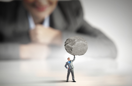 oppressed: Businesswoman looking at miniature of businessman lifting stone above head Stock Photo