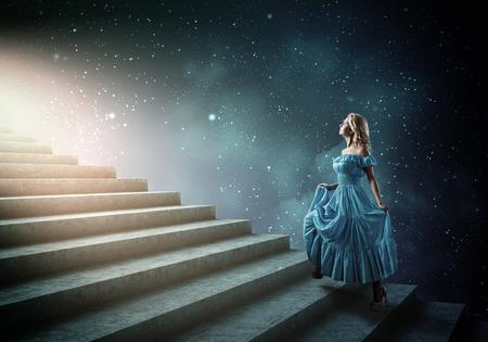 Jonge blonde vrouw in blauwe jurk lopen de trap op Stockfoto