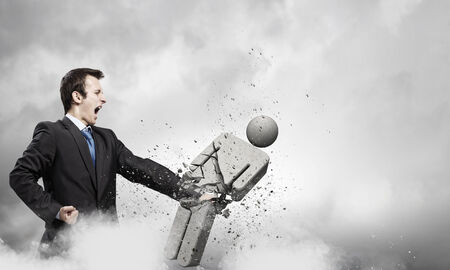 the opponent: Angry young businessman fighting with stone opponent Stock Photo
