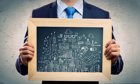 Close up of businessman holding frame with business sketches photo