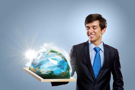 protecting your business: Apuesto hombre de negocios la celebraci�n de marco con el planeta Tierra. Foto de archivo