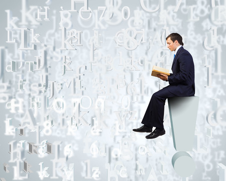 Young businessman sitting on exclamation mark and reading book photo