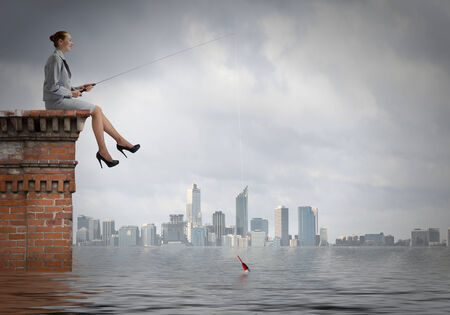 fisherwoman: Businesswoman fishing with rod on top of building
