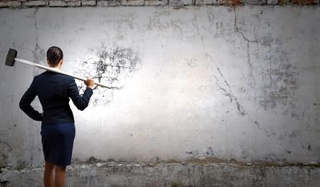 Junge attraktive Geschäftsfrau mit Hammer in der Hand Standard-Bild