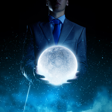 moonshine: Young businessman holding moon planet in hand