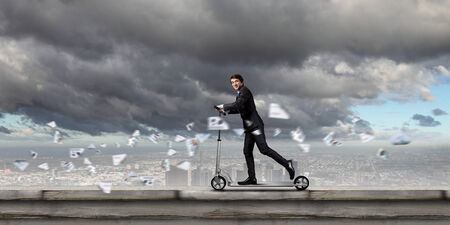 Young cheerful businessman riding scooter against city background photo