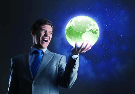 Young businessman holding digital globe in palm photo