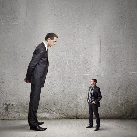Big bossy businessman looking down at small businessman Stock Photo - 28753852