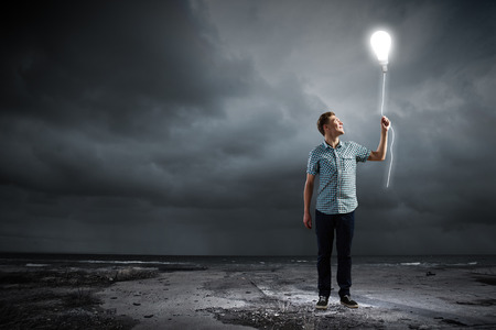 Young man and electrical bulb against dark background photo