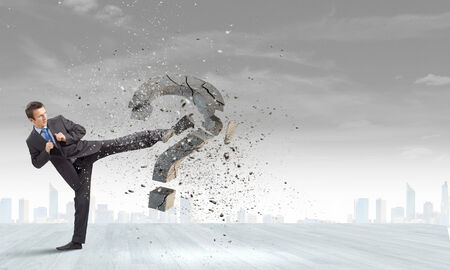 determinism: Businessman breaking stone question mark with karate kick Stock Photo