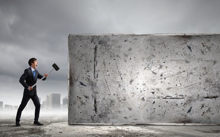 Young determined businessman breaking wall with hammer Stock Photo