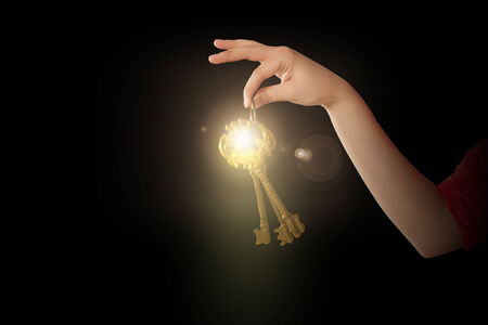 Close up of woman hand holding golden key photo