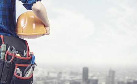 building maintenance: Close up of woman mechanic with yellow helmet in hand against city background