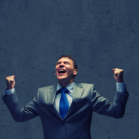 joyfully: Successful businessman screaming joyfully in to sky