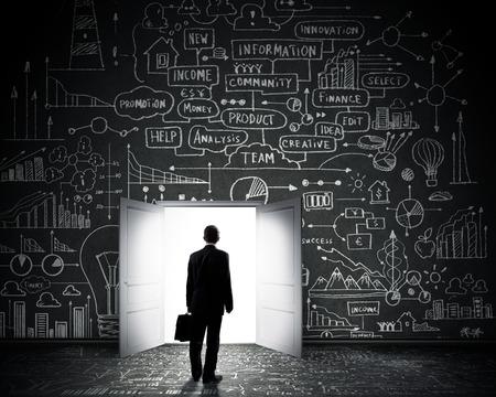 Rear view of businessman entering opened door in black wall