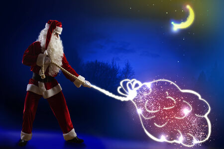 Santa Claus with big bag of gifts against night background photo