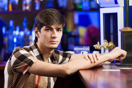 Young man in shirt sitting at bar photo