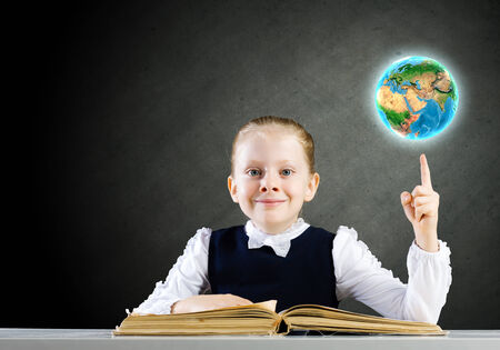 schoolkid search: Schoolgirl looking in opened book with sketches at background  Elements of this image are furnished by NASA Stock Photo