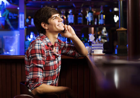 Young handsome man in casual sitting at bar and talking on phone photo