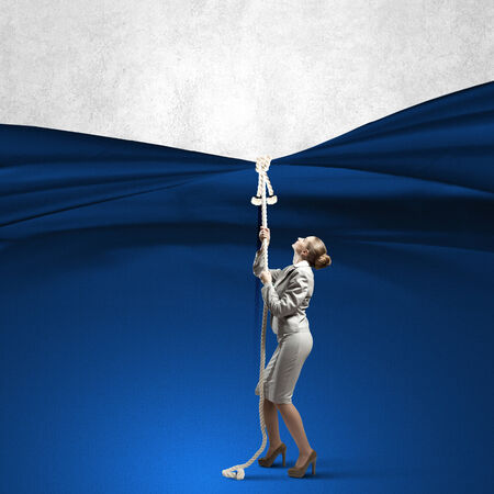 commercialism: Young businesswoman pulling curtain with rope  Place for text
