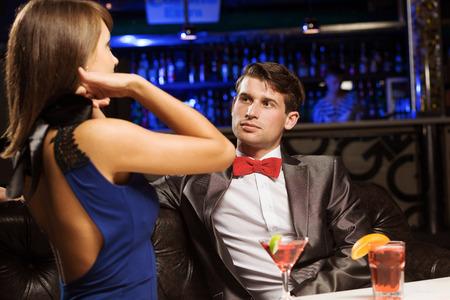 vergezeld: Jonge knappe man in bar vergezeld van elegante dame Stockfoto