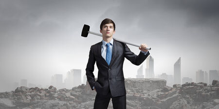 Young determined businessman with hammer in hands photo