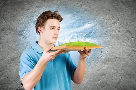 Young man in casual holding opened book with windmills photo
