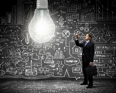 Businessman pointing at light bulb with business sketches at background photo