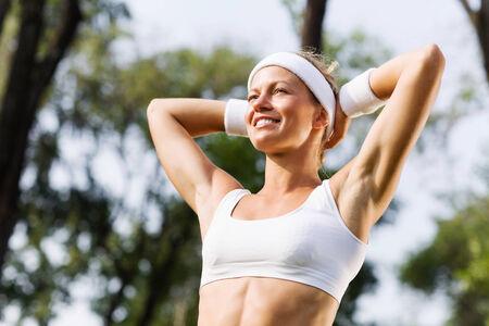 sport wear: La muchacha del deporte atractiva joven en el desgaste blanco del deporte en el parque Foto de archivo