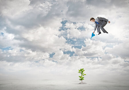 Young businessman standing on cloud and watering sprout photo