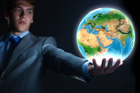 Young businessman holding Earth planet in hand  Elements of this image are furnished by NASA Banco de Imagens