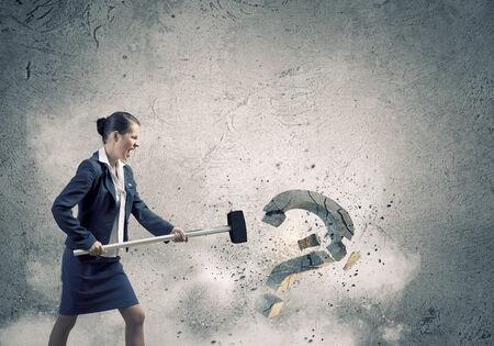 Young pretty businesswoman crashing stone question symbol photo