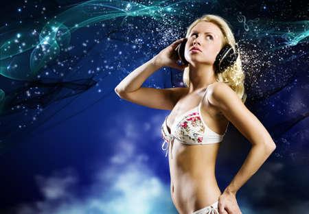 Young pretty woman in white bikini wearing headphones photo