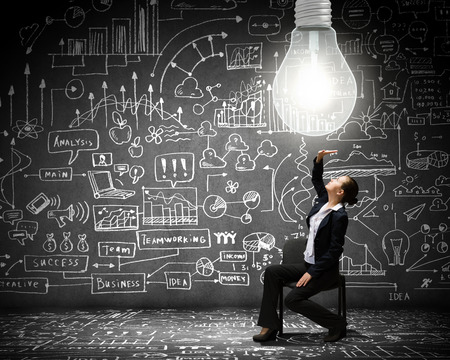 Young businesswoman sitting on chair with big light bulb above photo