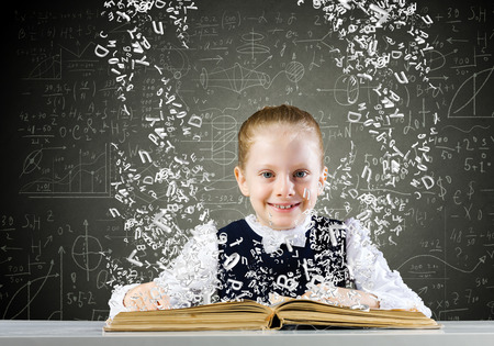 Cute school girl with opened book and sketches at background photo