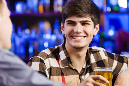 Two young men sitting at bar and talking photo