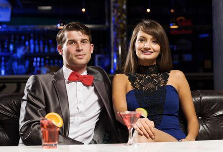 vergezeld: Jonge knappe man in de bar vergezeld van elegante dame