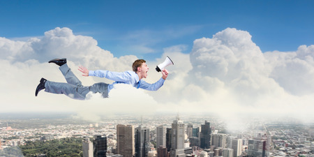 Young businessman with megaphone flying high in sky photo