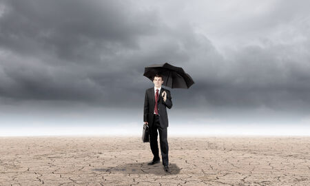 Young businessman with umbrella protecting sprout growing in desert photo