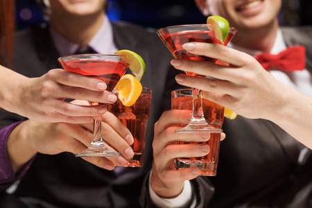 company party: Young attractive people of four having cocktail party