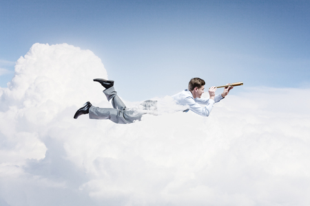 Young businessman flying in sky and lokking at spyglass photo