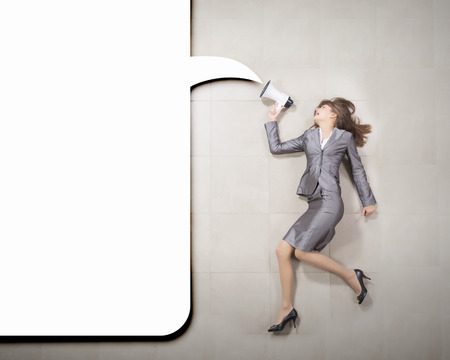 Funny image of businesswoman running with megaphone in hands photo