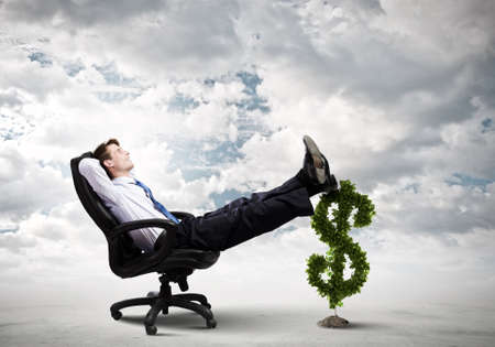 Young confident businessman sitting in chair with legs on dollar sign photo