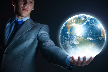 Young businessman holding Earth planet in hand  Elements of this image are furnished by NASA photo